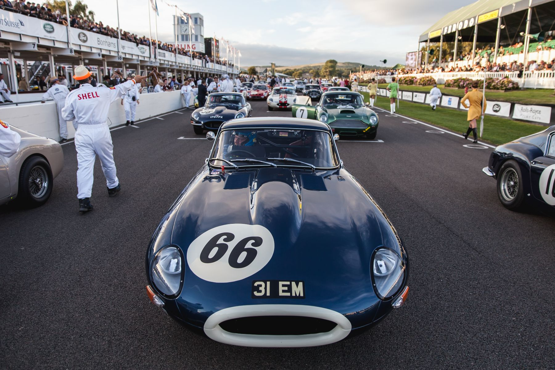A Jaguar E-Type on the grid surrounded by more E-Types, Aston Martin DB4 GTs and Ferrari 250 GT SWBs. Taken by Tim Brown for Goodwood