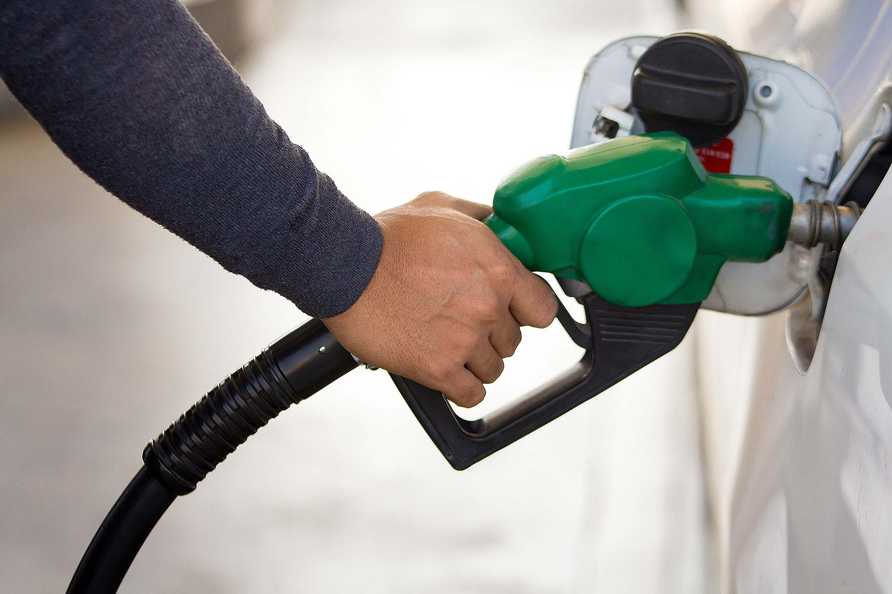 Person filling a car with unleaded petrol