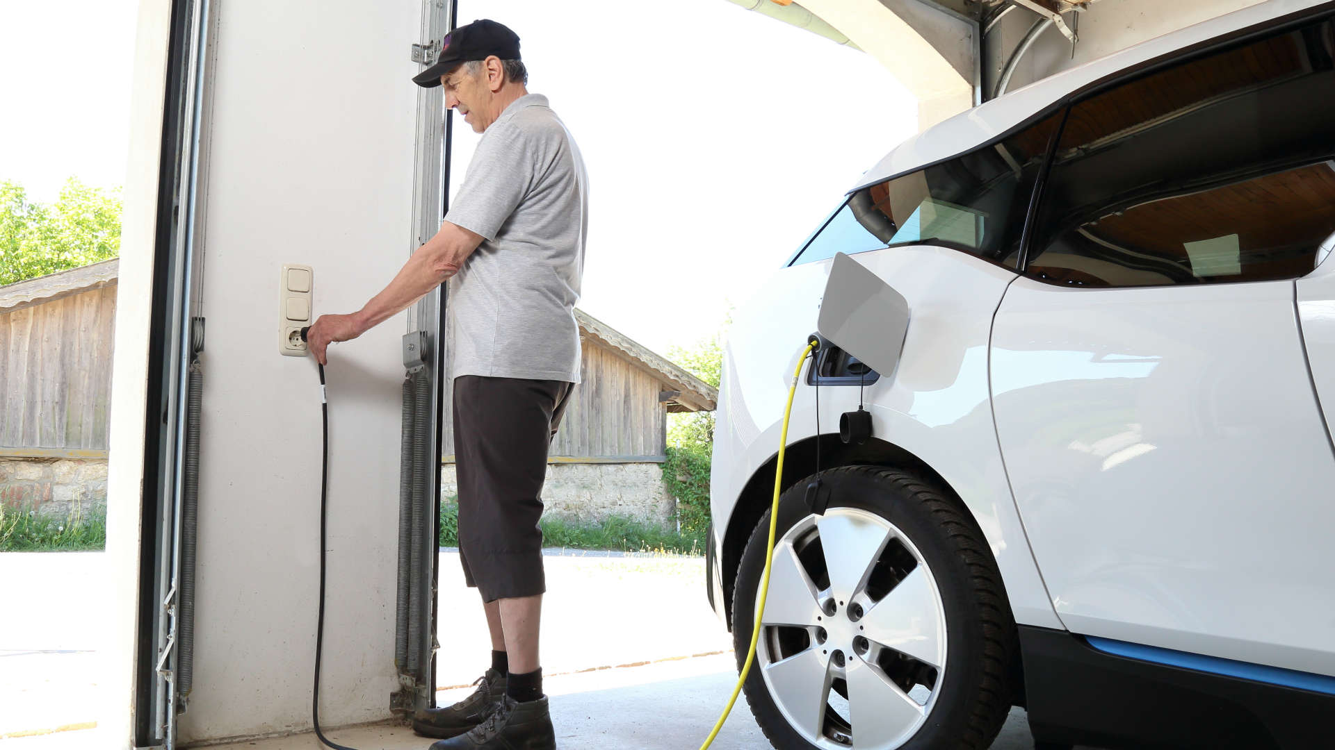 Man charging BMW i3 at home