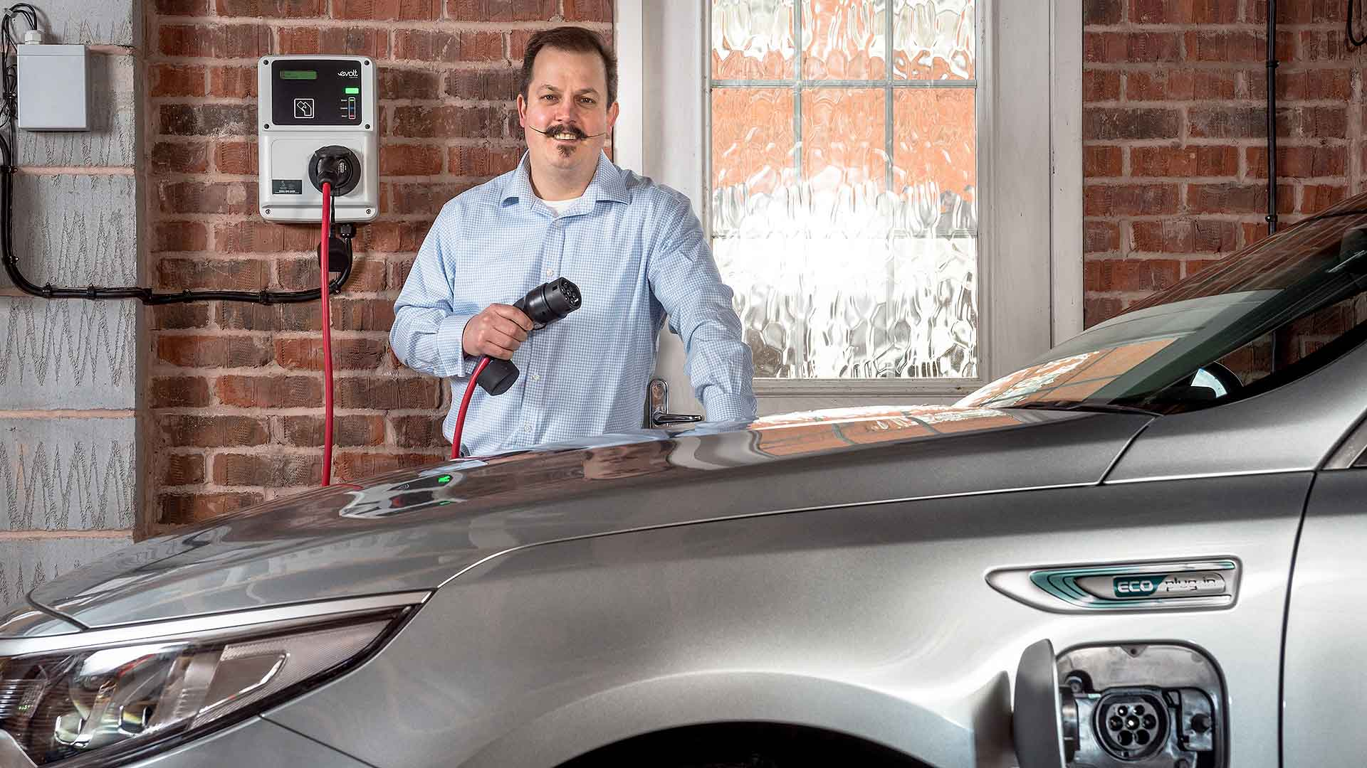 Electric car owner unplugging their vehicle
