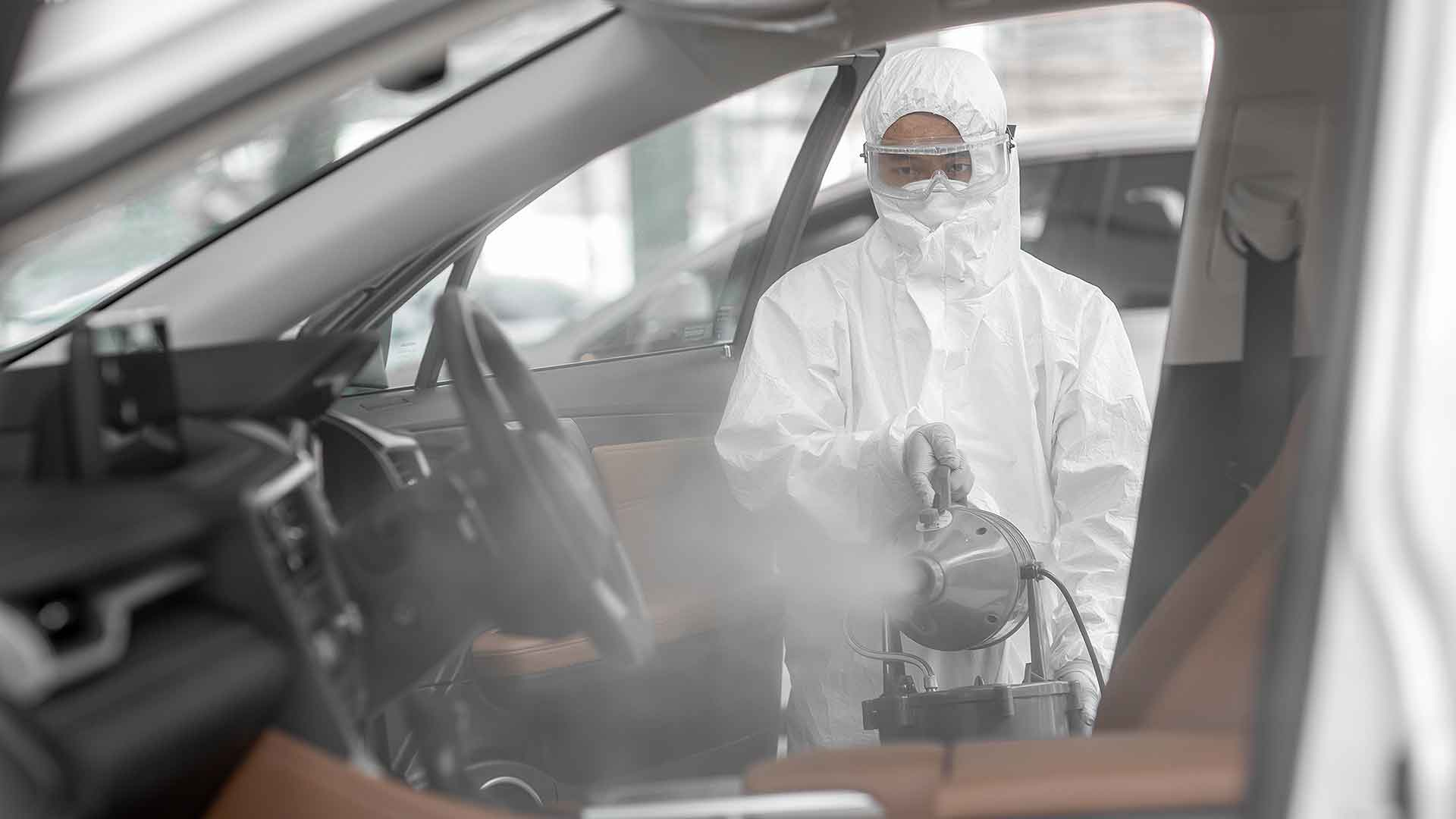 Technician spraying an anti-baterial mist into a vehicle
