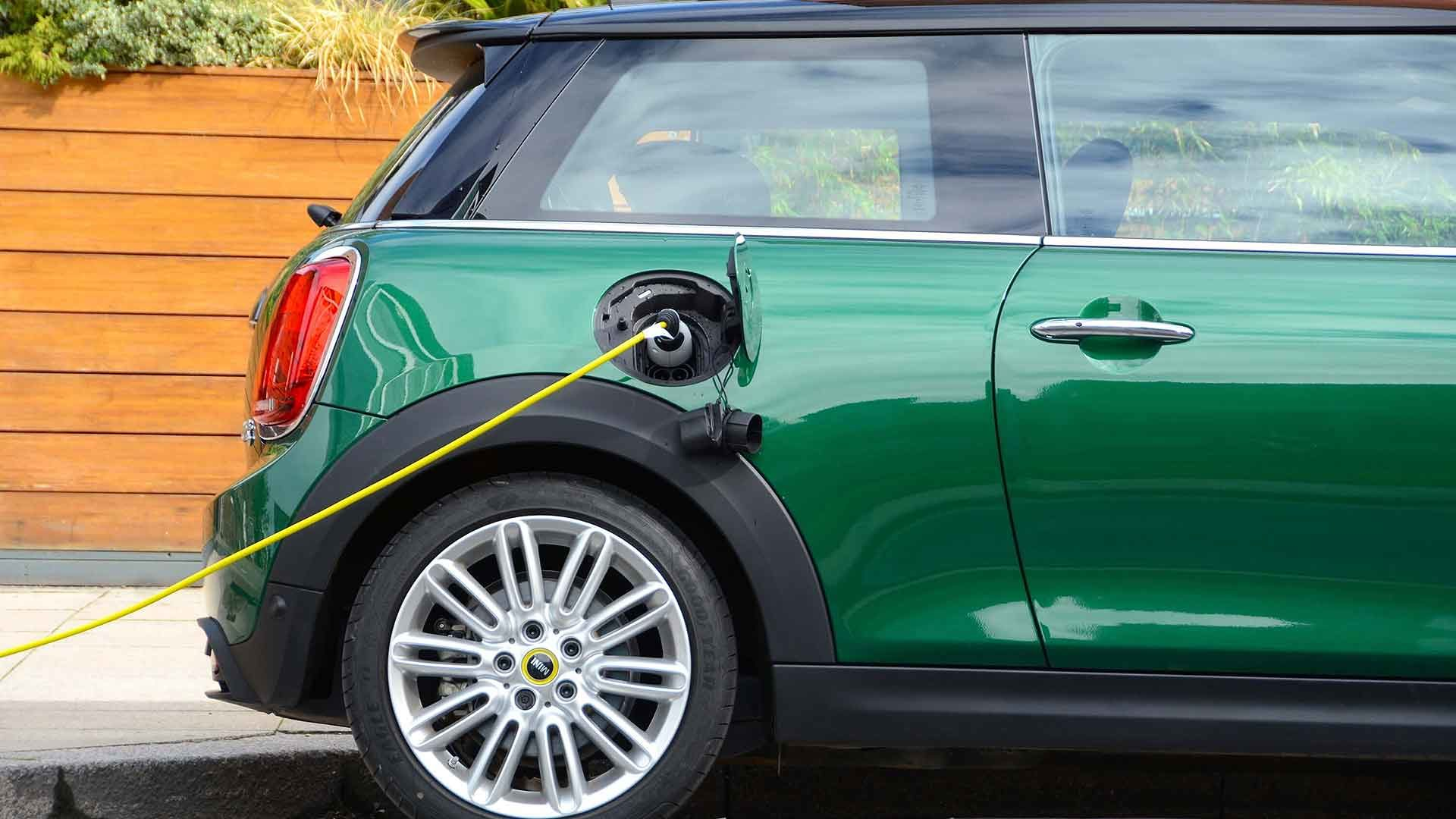 Green Mini Electric plugged into an electric car charger