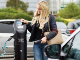 Young woman using a BP Chargemaster charging post