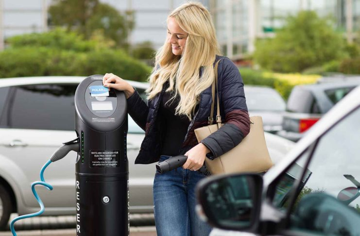 Young woman using a BP Chargemaster charging post